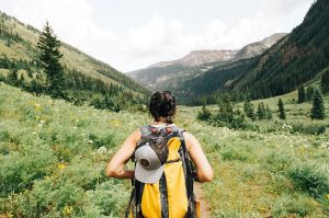 girl hiking with yellow backpack